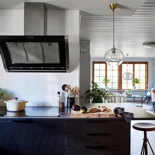 他の地域の大きいモダンスタイルのおしゃれなキッチン (ドロップインシンク、フラットパネル扉のキャビネット、黒いキャビネット、白いキッチンパネル、セラミックタイルのキッチンパネル、シルバーの調理設備の、濃色無垢フローリング、茶色い床、グレーのキッチンカウンター) の写真