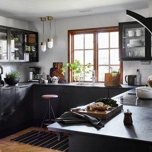 Bild på ett stort skandinaviskt svart svart kök, med släta luckor, svarta skåp, vitt stänkskydd, stänkskydd i keramik, brunt golv, en undermonterad diskho, svarta vitvaror och mellanmörkt trägolv