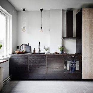 Bild på ett litet minimalistiskt linjärt kök med öppen planlösning, med en enkel diskho, släta luckor, skåp i slitet trä, träbänkskiva, stänkskydd i kalk, integrerade vitvaror, vinylgolv och grått golv