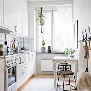 Réalisation d'une petite cuisine américaine linéaire nordique avec un placard à porte plane, des portes de placard blanches, un plan de travail en inox, une crédence blanche, un sol en linoléum, aucun îlot et un sol beige.