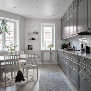 Idéer för ett skandinaviskt vit linjärt kök och matrum, med luckor med upphöjd panel, grå skåp, marmorbänkskiva, vitt stänkskydd, stänkskydd i tunnelbanekakel, integrerade vitvaror, ljust trägolv och beiget golv