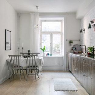 Idéer för ett mellanstort skandinaviskt beige linjärt kök och matrum, med släta luckor, skåp i mörkt trä, vitt stänkskydd, integrerade vitvaror, ljust trägolv, beiget golv, stänkskydd i tunnelbanekakel och en enkel diskho