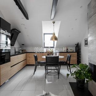 Minimalistisk inredning av ett mellanstort kök, med släta luckor, grå skåp, vitt stänkskydd, stänkskydd i tunnelbanekakel och svarta vitvaror