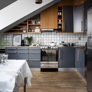 Nordisk inredning av ett mellanstort kök, med släta luckor, blå skåp, vitt stänkskydd, rostfria vitvaror, mellanmörkt trägolv och stänkskydd i keramik