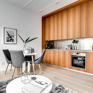 Modern inredning av ett mellanstort linjärt kök med öppen planlösning, med släta luckor, skåp i mellenmörkt trä, stänkskydd i metallkakel, integrerade vitvaror och ljust trägolv