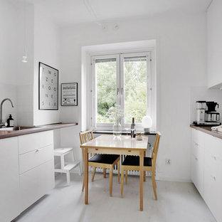 Idéer för att renovera ett minimalistiskt kök, med en nedsänkt diskho, släta luckor, vita skåp, träbänkskiva, vitt stänkskydd, stänkskydd i tunnelbanekakel, rostfria vitvaror, ljust trägolv och vitt golv