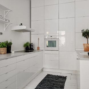 Inspiration för mellanstora nordiska parallellkök, med en enkel diskho, släta luckor, vita skåp, vita vitvaror och målat trägolv