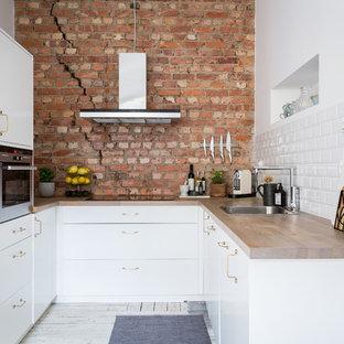 Inredning av ett skandinaviskt avskilt l-kök, med en nedsänkt diskho, släta luckor, vita skåp, träbänkskiva, vitt stänkskydd, stänkskydd i tunnelbanekakel, rostfria vitvaror, målat trägolv och vitt golv