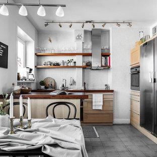Bild på ett mellanstort minimalistiskt brun brunt kök, med skåp i ljust trä, grått stänkskydd, stänkskydd i mosaik, en halv köksö, grått golv, skåp i shakerstil, träbänkskiva och rostfria vitvaror