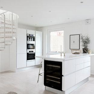 Inredning av ett skandinaviskt mellanstort linjärt kök med öppen planlösning, med släta luckor, vita skåp, svarta vitvaror, ljust trägolv, en köksö och vitt golv