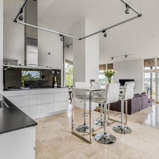 Modern inredning av ett kök, med en enkel diskho, släta luckor, vita skåp, bänkskiva i onyx, vitt stänkskydd, glaspanel som stänkskydd och beiget golv
