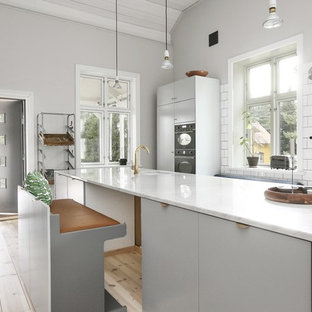 Inredning av ett nordiskt kök med öppen planlösning, med en undermonterad diskho, släta luckor, grå skåp, vitt stänkskydd, ljust trägolv, en köksö och beiget golv