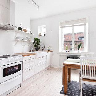 Idéer för mellanstora skandinaviska linjära kök och matrum, med en rustik diskho, luckor med infälld panel, vita skåp, träbänkskiva, vitt stänkskydd, rostfria vitvaror och ljust trägolv