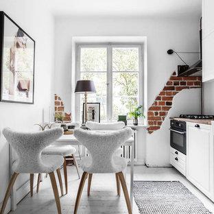 Exempel på ett mellanstort minimalistiskt linjärt kök och matrum, med vitt golv, en rustik diskho, luckor med upphöjd panel, vita skåp, svarta vitvaror och målat trägolv
