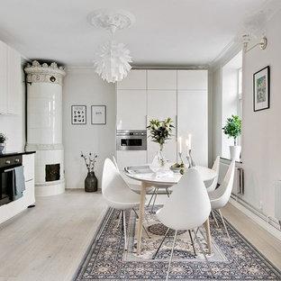 Idéer för att renovera ett mellanstort minimalistiskt kök, med släta luckor, vita skåp, stänkskydd i mosaik, integrerade vitvaror, ljust trägolv, vitt stänkskydd och vitt golv