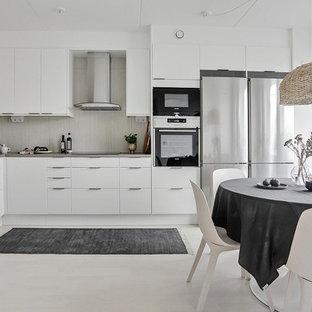 Idéer för ett nordiskt grå kök, med släta luckor, vita skåp, grått stänkskydd, rostfria vitvaror och beiget golv