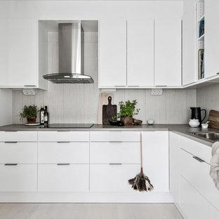 Inspiration för mellanstora nordiska grått l-kök, med släta luckor, vita skåp, grått stänkskydd, en dubbel diskho, svarta vitvaror och beiget golv