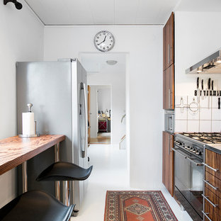 Small traditional enclosed kitchen remodeling - Example of a small classic single-wall white floor enclosed kitchen design in Malmo with flat-panel cabinets, medium tone wood cabinets, stainless steel countertops, white backsplash and no island