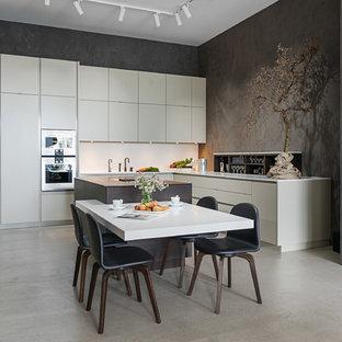 Modern inredning av ett stort vit vitt kök, med en undermonterad diskho, släta luckor, bänkskiva i koppar, vitt stänkskydd, rostfria vitvaror, betonggolv, en köksö, grått golv och vita skåp