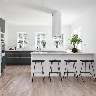Inspiration för mellanstora moderna vitt u-kök, med en undermonterad diskho, släta luckor, svarta skåp, en halv köksö och beiget golv