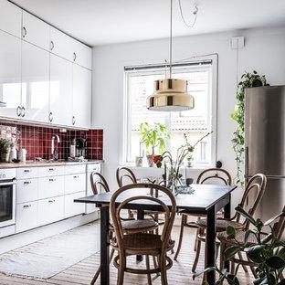 Nordisk inredning av ett linjärt kök och matrum, med släta luckor, vita skåp, träbänkskiva, rött stänkskydd, ljust trägolv, beiget golv, en nedsänkt diskho, stänkskydd i keramik och rostfria vitvaror