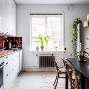 Scandinavian eat-in kitchen remodeling - Danish single-wall light wood floor and beige floor eat-in kitchen photo in Gothenburg with white cabinets, wood countertops, red backsplash, stainless steel appliances and no island