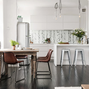 Mid-sized scandinavian l-shaped open plan kitchen in Gothenburg with flat-panel cabinets, white cabinets, stainless steel appliances, a peninsula, laminate benchtops and dark hardwood floors.