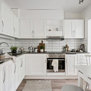 Idéer för ett mellanstort minimalistiskt kök, med luckor med profilerade fronter, vita skåp, bänkskiva i rostfritt stål och vitt stänkskydd