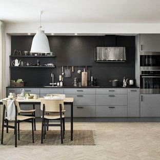 Idéer för att renovera ett skandinaviskt svart linjärt svart kök och matrum, med en undermonterad diskho, släta luckor, grå skåp, svart stänkskydd, integrerade vitvaror, ljust trägolv och beiget golv