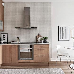 Foto på ett nordiskt kök, med en nedsänkt diskho, släta luckor, skåp i ljust trä, stänkskydd i mosaik, rostfria vitvaror, ljust trägolv och vitt stänkskydd