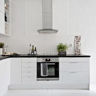 Inredning av ett nordiskt mellanstort kök, med släta luckor, vita skåp, laminatbänkskiva, vitt stänkskydd, målat trägolv, vitt golv, en nedsänkt diskho och rostfria vitvaror