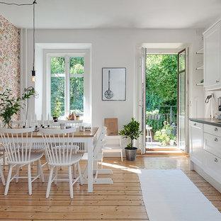 Новый формат декора квартиры: линейная кухня среднего размера в скандинавском стиле с обеденным столом, двойной раковиной, стеклянными фасадами, белыми фасадами, белым фартуком, паркетным полом среднего тона и столешницей из нержавеющей стали без острова