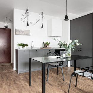 Exempel på ett litet nordiskt kök, med mellanmörkt trägolv, brunt golv, släta luckor och grå skåp