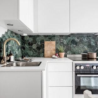 Inspiration för små moderna l-kök, med en nedsänkt diskho, släta luckor, vita skåp, grönt stänkskydd, stänkskydd i mosaik och rostfria vitvaror