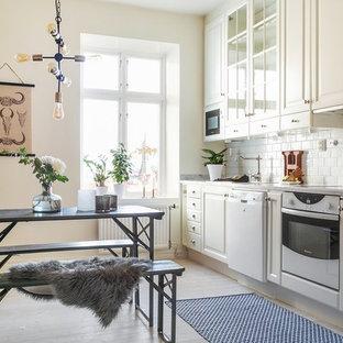 Idéer för ett minimalistiskt linjärt kök och matrum, med luckor med glaspanel, vitt stänkskydd, stänkskydd i porslinskakel, vita vitvaror, beige skåp, ljust trägolv och beiget golv