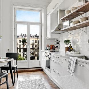 Inredning av ett skandinaviskt mellanstort linjärt kök och matrum, med en undermonterad diskho, släta luckor, vita skåp, vitt stänkskydd, stänkskydd i tunnelbanekakel, rostfria vitvaror, mellanmörkt trägolv och en köksö