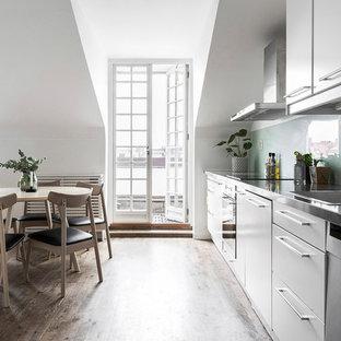 Inspiration för mellanstora nordiska linjära kök med öppen planlösning, med mellanmörkt trägolv, brunt golv, en nedsänkt diskho, släta luckor, vita skåp, blått stänkskydd, glaspanel som stänkskydd och rostfria vitvaror