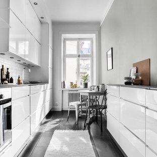 Idéer för ett minimalistiskt svart kök, med släta luckor, vita skåp, vitt stänkskydd, stänkskydd i tunnelbanekakel och svart golv