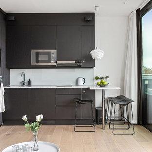 Idéer för att renovera ett mellanstort funkis vit vitt l-kök, med en undermonterad diskho, släta luckor, grå skåp, vitt stänkskydd, glaspanel som stänkskydd, rostfria vitvaror, ljust trägolv, en halv köksö och beiget golv