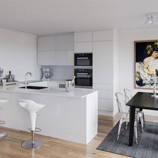 Bild på ett mellanstort funkis vit vitt kök, med en undermonterad diskho, släta luckor, vita skåp, vitt stänkskydd, rostfria vitvaror, mellanmörkt trägolv, en halv köksö och beiget golv