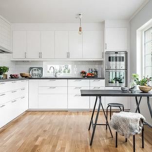 Idéer för att renovera ett nordiskt kök och matrum, med släta luckor, vita skåp, vitt stänkskydd, stänkskydd i tunnelbanekakel, rostfria vitvaror, mellanmörkt trägolv och brunt golv