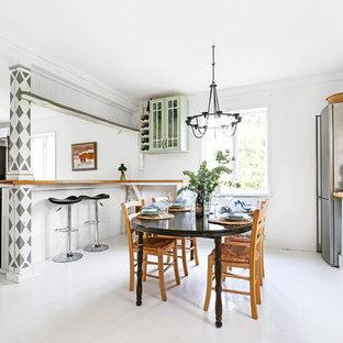 Minimalistisk inredning av ett mellanstort linjärt kök med öppen planlösning, med gröna skåp, träbänkskiva, vitt stänkskydd, rostfria vitvaror, en halv köksö, vitt golv och målat trägolv