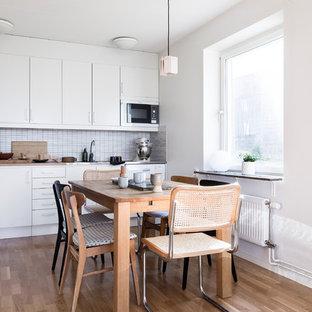 Inspiration för ett minimalistiskt kök, med släta luckor, vita skåp, grått stänkskydd, vita vitvaror, mörkt trägolv, brunt golv och stänkskydd i mosaik