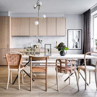 Inredning av ett minimalistiskt stort linjärt kök och matrum, med släta luckor, skåp i ljust trä, stänkskydd i marmor, integrerade vitvaror och mellanmörkt trägolv