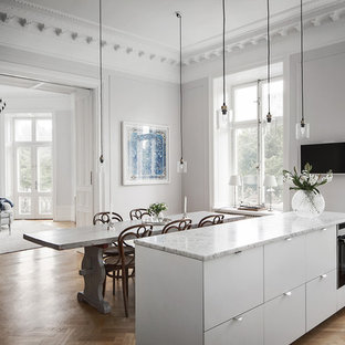 Large victorian eat-in kitchen photos - Inspiration for a large victorian single-wall medium tone wood floor eat-in kitchen remodel in Stockholm with marble countertops, stainless steel appliances and an island