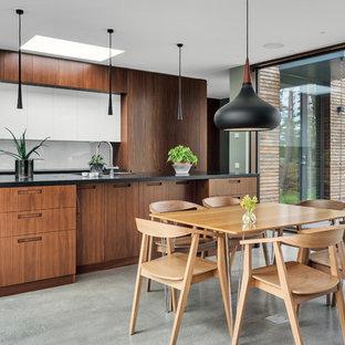 Idéer för mellanstora funkis svart kök, med släta luckor, skåp i mellenmörkt trä, betonggolv, en köksö, grått golv, en undermonterad diskho, vitt stänkskydd och svarta vitvaror