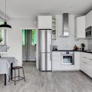 Exempel på ett minimalistiskt svart svart kök, med släta luckor, vita skåp, vitt stänkskydd, grått golv, en undermonterad diskho, stänkskydd i tunnelbanekakel, rostfria vitvaror och ljust trägolv