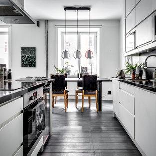 Idéer för att renovera ett mellanstort skandinaviskt kök, med släta luckor, vita skåp, mörkt trägolv och en halv köksö