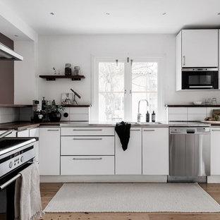 Inredning av ett skandinaviskt mellanstort brun brunt kök, med släta luckor, vita skåp, en dubbel diskho, träbänkskiva, vitt stänkskydd, rostfria vitvaror, ljust trägolv och beiget golv