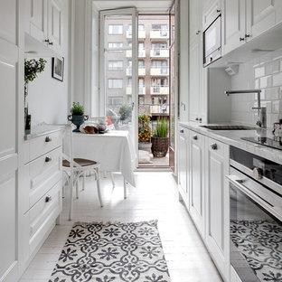 Zweizeilige, Mittelgroße Skandinavische Wohnküche mit Unterbauwaschbecken, profilierten Schrankfronten, weißen Schränken, Küchenrückwand in Weiß, Rückwand aus Metrofliesen, Küchengeräten aus Edelstahl, gebeiztem Holzboden und Marmor-Arbeitsplatte in Stockholm
